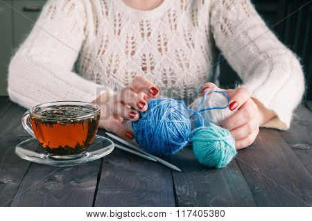 Woman Hands With Cup Of Tea And Wool Yarn Balls On A Wooden Table.
