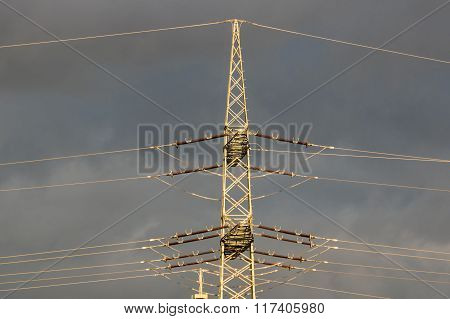 high-voltage electricity pylons against rain clouds