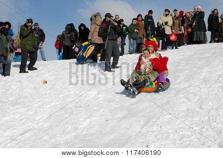 Gatchina, Leningrad region, RUSSIA - March 5, 2011: Maslenitsa. Riding a roller coaster.