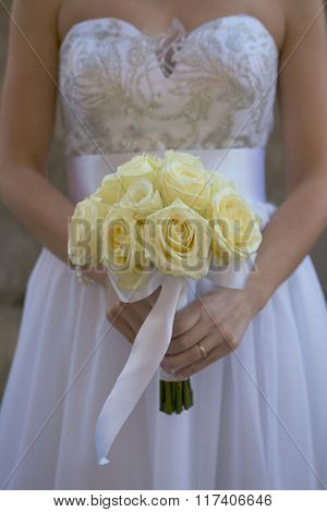 Bride holding white wedding bouquet of roses (muted colors)
