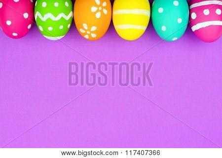 Easter egg top border over purple paper background