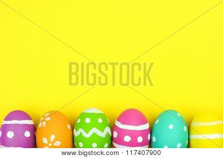 Easter egg bottom border over yellow paper background