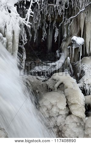 Frozen waterfall view in winter with river flowing and beautiful icicles