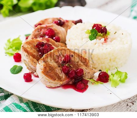 Pork Medallions Steak With Cranberry Sauce And A Side Dish Of Rice