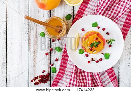 Fruit Salad With Grapefruit And Orange, Pomegranate Seeds, Honey And Lemon, Decorated With Mint. Top