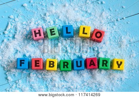 Hello February written on colour wooden toy cubes On light background with snow
