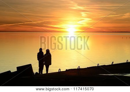 Couple silhouette with orange sea sunset background