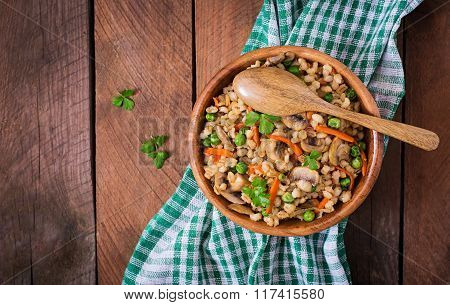 Vegetarian Crumbly Pearl Barley Porridge With Mushrooms And Green Peas In A Wooden Bowl. Top View