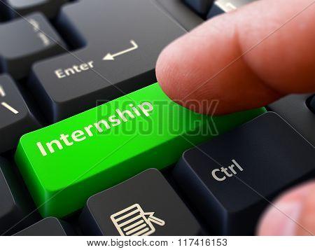 Pressing Green Button Internship on Black Keyboard.