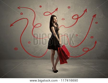 An elegant young lady in black holding red shopping bags in front of urban wall background with drawn red arrows and circles concept