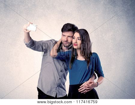 A young couple in love taking selfie with a mobile phone in the handsome guy's hand in front of an empty clear grey wall background concept