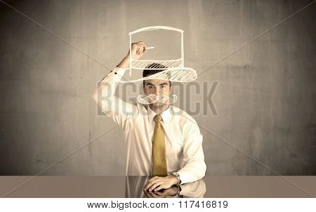 A young happy businessman in elegant suit drawing funny hat and mustache in empty grey space with a chalk illustration concept