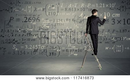 A businessman in elegant suit standing on a small ladder and writing numbers, calculating on grey wall background