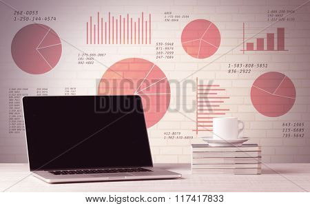A professional laptop with blank screen sitting on a white office desk in front of wall full of pie charts and graphs concept