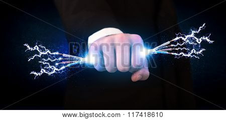 Business person holding electrical powered wires concept on background