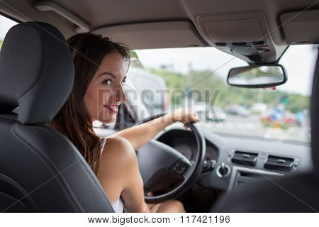 Young, attractive woman driving a car, going home from work