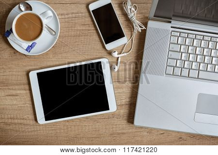 Laptop smartphone and coffee cup on wood background