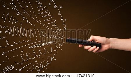 Hand holding a remote control, curly lines and arrows coming out of it