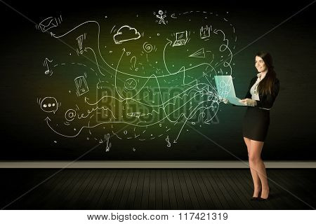 Businesswoman sitting in chair holding laptop with media icons concept on background