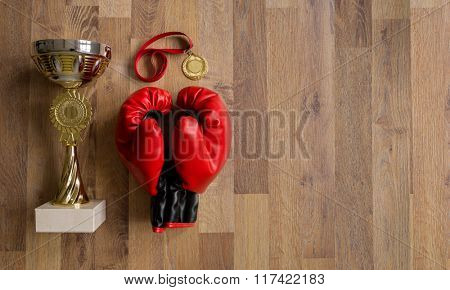 boxing gloves and trophies on wooden planks background