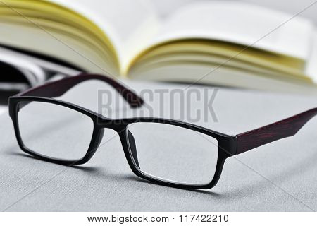 closeup of a pair of eyeglasses and an open book in the background