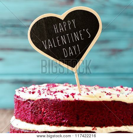closeup of a red velvet cake topped with a heart-shaped chalkboard with the text happy valentines day written in it, against a blue rustic wooden background