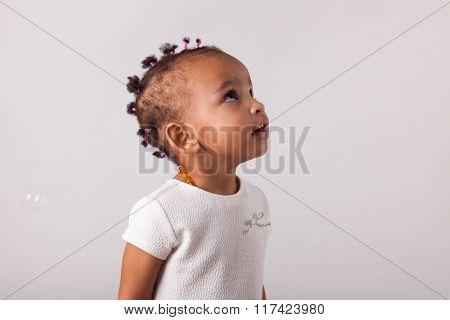 Portrait Of Little African American Little Girl Playing With Soap Bubbles