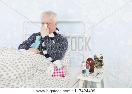 Senior man sick in bed with hot water bottle and thermometer