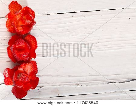 Ornament From Three Red Roses Which Are Cut Out From Strawberry On The Edge Of A White Boar