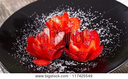 Three Roses From Ripe Strawberry On A Black Plate, Are Sugared