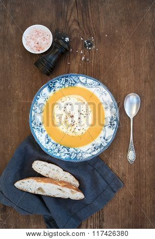 Homemade pumpkin cream soup in porcelain plate with spices and fresh bread slices on over rustic woo