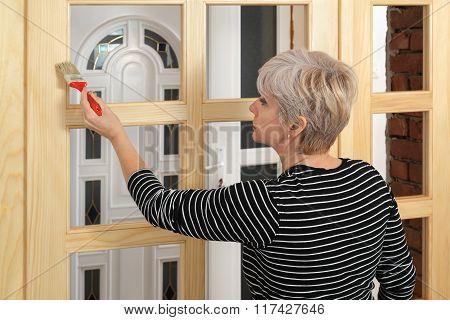 Adult Female Worker Painting  Wooden Door