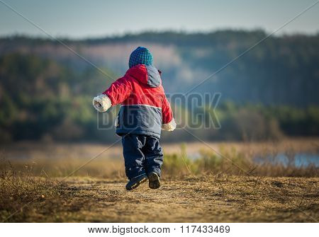 Young Happy Boy Playing And Jumping In Outdoor