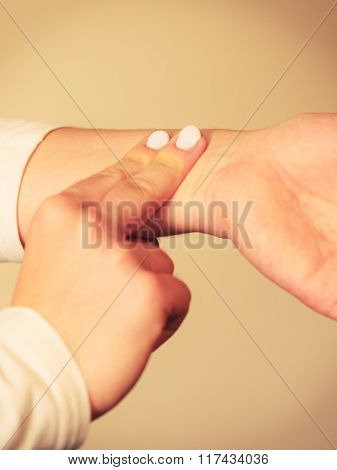 Woman Checking Pulse On Wrist Closeup