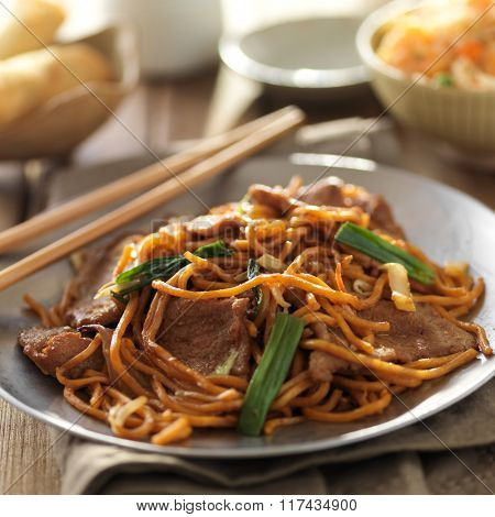 plate of chinese beef lo mein with chopsticks