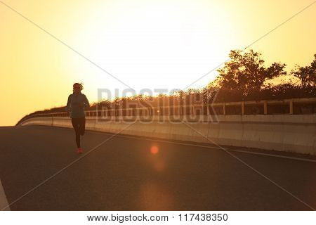 young fitness woman runner running on sunrise road