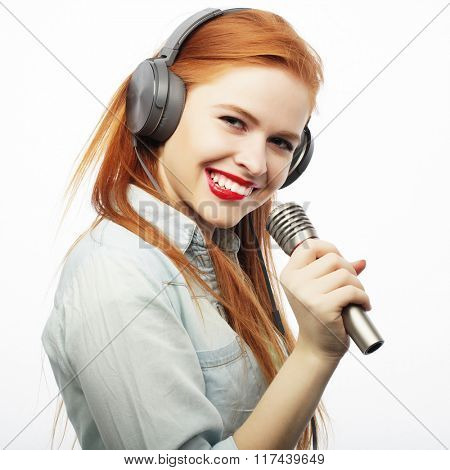 Beautiful young woman with microphone and headphones