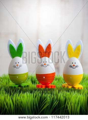 Three colorful easter bunny on the green grass