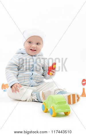 caucasian baby boy child playing with cars warm clothing hat sitting isolated on white studio shot