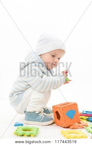 little child baby playing puzzles isolated on white studio shot