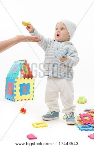 little child baby playing with puzzles isolated on white studio shot
