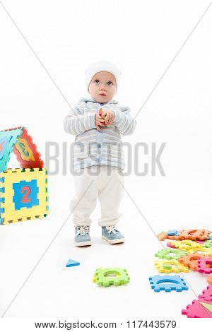 little child baby playing with puzzles warm cloth hat isolated on white studio shot