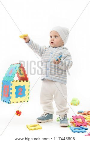 little child baby boy playing with puzzles isolated on white studio shot