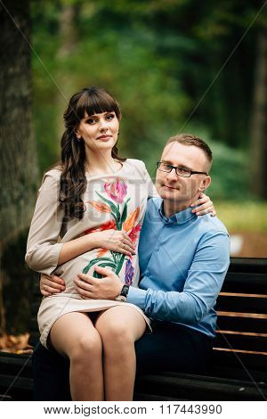 Beautiful And Happy Pregnant Couple Relaxing Outside In The Autumn Park Sitting On Bench.