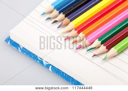 Row Of Color Pencils On A Blank Notebook