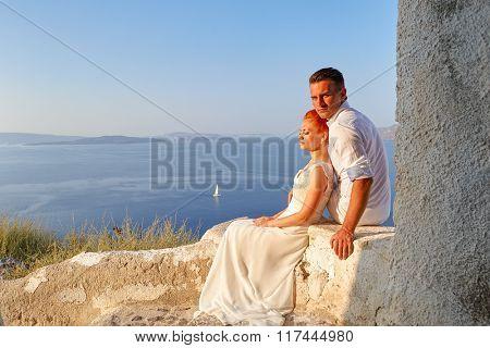Beautiful young couple bride and groom posing on Santorini island, Greece