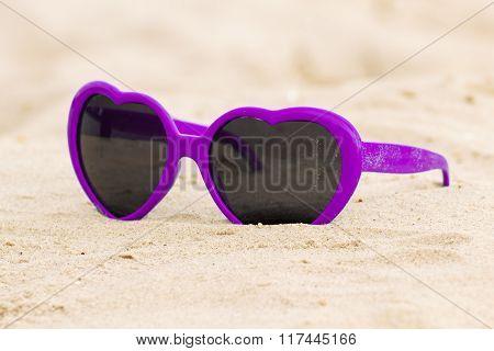 Purple Sunglasses Shaped Heart On The Sand