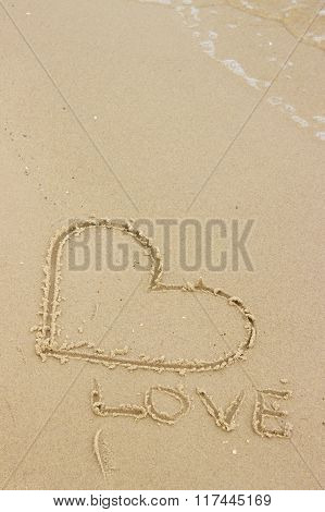 Word Love And Heart Written On Sand At The Beach By The Sea