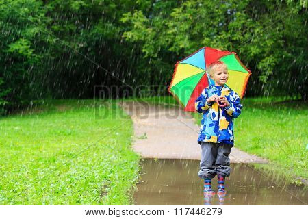 little boy with colorful umbrella outdoors