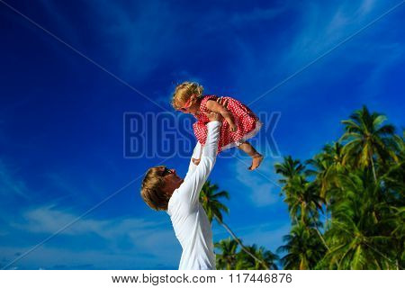 father and little daughter play on sky at tropical beach